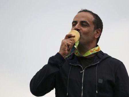 Foto del miércoles del kuwaití Fehaid Aldeehani besando la medalla de oro que ganó en la prueba de doble foso en los Juegos de Río. Ago 10, 2016. El veterano kuwaití Fehaid Aldeehani luchó contra las condiciones húmedas y ventosas para ganar el miércoles el evento masculino de doble foso del tiro olímpico de Río, convirtiéndose además en el primer atleta que compite bajo la bandera olímpica en lograr una medalla de oro. REUTERS/Edgard Garrido